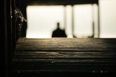 La siluetta dell'uomo che cammina su un ponte di legno Fotografie Stock Libere da Diritti