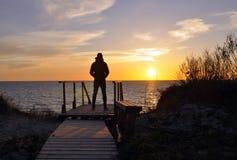 La siluetta dell'uomo che sta da solo alla spiaggia fotografie stock