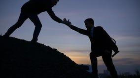 La siluetta dell'uomo d'affari gived la mano affinchè il gruppo di tirata alzi insieme il lavoro verticalmente della montagna video d archivio