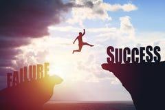 La siluetta dell'uomo di affari salta al testo di successo sopra un fondo della montagna di bella vista immagini stock libere da diritti