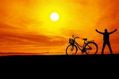 La siluetta dell'uomo e della bici durante il tramonto fotografia stock