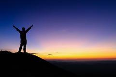La siluetta dell'uomo sta stando e mano di diffusione sopra la montagna Fotografie Stock