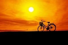 La siluetta della bici e del cielo arancio al tramonto immagini stock libere da diritti