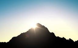 La siluetta della cima della montagna sopra il cielo ed il sole si accendono Immagini Stock