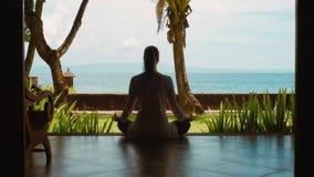 La siluetta della donna che si rilassa praticando l'yoga nella posizione di loto dal bungalow sulla spiaggia dell'oceano, la bell archivi video