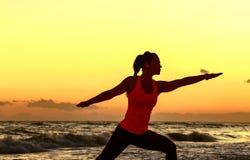 La siluetta della donna di misura nello sport copre sull'allungamento della spiaggia Fotografia Stock