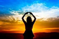 La siluetta della donna effettua come yoga Immagine Stock Libera da Diritti