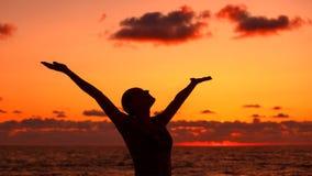 La siluetta della donna sopra il tramonto fotografia stock