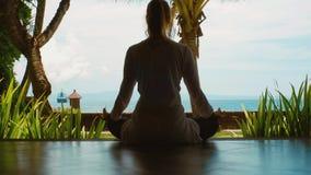 La siluetta della donna sta praticando l'yoga che si rilassa nella posizione di loto sulla spiaggia dell'oceano, bella vista, suo stock footage
