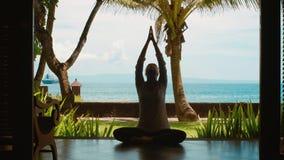 La siluetta della donna sta praticando la meditazione di yoga nella posizione di loto, allunga le mani su sulla spiaggia, bella v archivi video