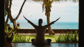 La siluetta della donna sta praticando la meditazione di yoga nella posizione di loto sulla spiaggia dell'oceano, bella vista, su video d archivio
