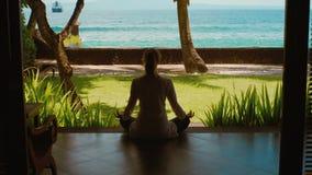 La siluetta della donna sta rilassandosi praticando l'yoga nella posizione di loto dal bungalow sulla spiaggia dell'oceano con la stock footage