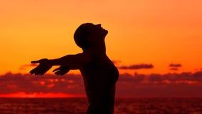 La siluetta della donna sul fondo di tramonto immagini stock