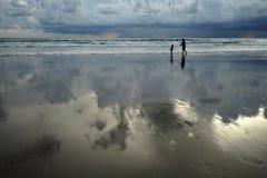 La siluetta della famiglia che gioca sulla spiaggia Fotografie Stock Libere da Diritti