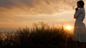 La siluetta della figura della giovane donna che prega a Dio al tramonto, la ragazza ha piegato le sue mani al mento nel campo, c archivi video