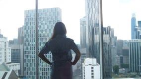 La siluetta della giovane donna ammira la vista della città dalla finestra in ufficio fotografia stock libera da diritti