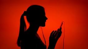 La siluetta della giovane donna messa sui trasduttori auricolari ed ascolta musica sullo Smart Phone su fondo rosso archivi video