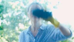 La siluetta della giovane donna spruzza il detersivo sulla finestra sporca video d archivio