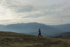 La siluetta della ragazza esile sta pareggiando in montagne nebbiose fotografia stock