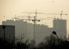 La siluetta delle case e molte gru le costruiscono immagine stock libera da diritti
