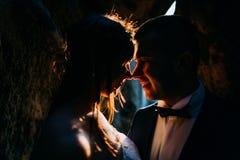La siluetta delle coppie bacianti vestite alla moda con fondo scuro, splesa di tramonto arancio irradia Immagini Stock