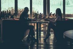La siluetta delle coppie di amore che si siedono in caffè Fotografia Stock Libera da Diritti