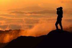 La siluetta delle donne sta prendendo una certa fotografia sulla montagna Immagini Stock Libere da Diritti