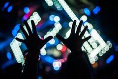La siluetta delle mani sollevate ed i braccia al festival di concerto fanno festa fotografie stock libere da diritti