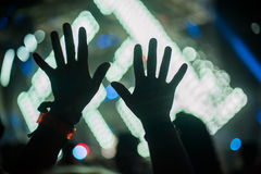 La siluetta delle mani sollevate ed i braccia al festival di concerto fanno festa fotografia stock libera da diritti