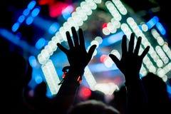 La siluetta delle mani sollevate ed i braccia al festival di concerto fanno festa immagini stock