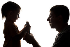 La siluetta delle relazioni di famiglia, il padre dà la matita di colore del bambino Fotografie Stock Libere da Diritti