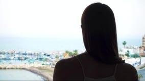 La siluetta delle tende aperte della donna e gode della vista del mare dal terrazzo Sguardo femminile del viaggiatore al porticci video d archivio