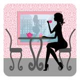 La siluetta di bella ragazza si siede in un caffè Fotografie Stock Libere da Diritti