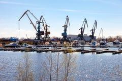 La siluetta di porto cranes contro il cielo blu e le imbarcazioni a motore a Fotografia Stock