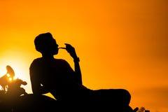 La siluetta di seduta dell'uomo del motociclista fuma con la sua motocicletta accanto al lago naturale e bello, godendo della lib Immagine Stock Libera da Diritti