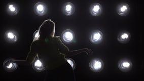 La siluetta di un dancing della ragazza sui precedenti si accende stock footage