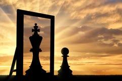 La siluetta di un pegno, si vede nella riflessione della regina dello specchio fotografia stock
