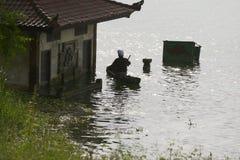 La siluetta di un uomo che rema verso una riva del lago alloggia sommerso Immagine Stock