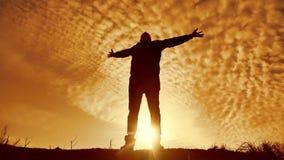 La siluetta di un uomo con le mani si è alzata nel concetto del tramonto per la religione, il culto, la preghiera e l'elogio Silu archivi video