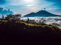 La siluetta di un viaggiatore su un fondo delle montagne e delle nuvole, vista laterale immagini stock