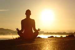 La siluetta di una donna di forma fisica che esercita la meditazione di yoga si esercita Fotografia Stock
