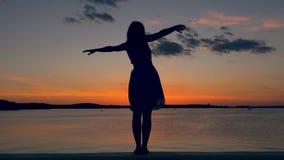 La siluetta di una donna ha sollevato le sue mani al lato sul lungomare al tramonto stock footage