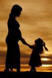 La siluetta di una donna incinta si tiene per mano con la piccola ragazza Fotografia Stock Libera da Diritti