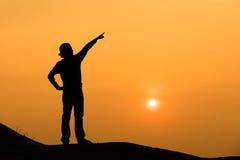 La siluetta di una donna indica la sua mano il cielo Fotografia Stock Libera da Diritti