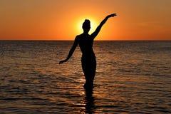 La siluetta di una femmina misteriosa dipende i precedenti del tramonto del mare fotografie stock