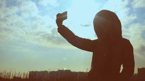 La siluetta di una giovane donna con i vetri sulla natura prende un selfie contro il contesto del tramonto e delle costruzioni stock footage