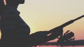 La siluetta di una giovane donna con una canna da pesca che fila in sue mani torce la bobina all'alba che estrae il fermo contro stock footage