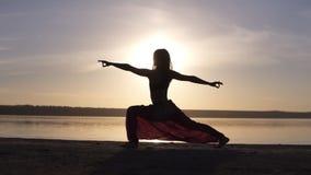 La siluetta di una ragazza snella fa la posa di yoga del namaste del guerriero al tramonto seaside stock footage