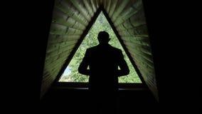 La siluetta di uno sposo che mette su un rivestimento, sul giro intorno e sull'allontanarsi Una retrovisione Una finestra triango video d archivio