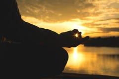 La siluetta di yoga della donna anziana vicino al lago durante il tramonto, si rilassa il tempo e l'esercizio Fotografie Stock